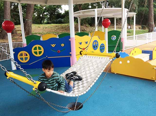 浦添大公園の新しい遊具のハンモックで遊ぶ男の子